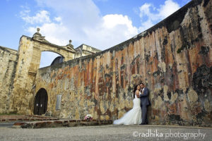 a bride and groom taking wedding photos at san cristobal fort in old san juan